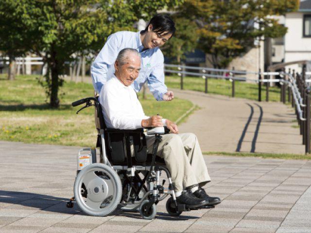 電動車椅子に乗るシニア男性と男性