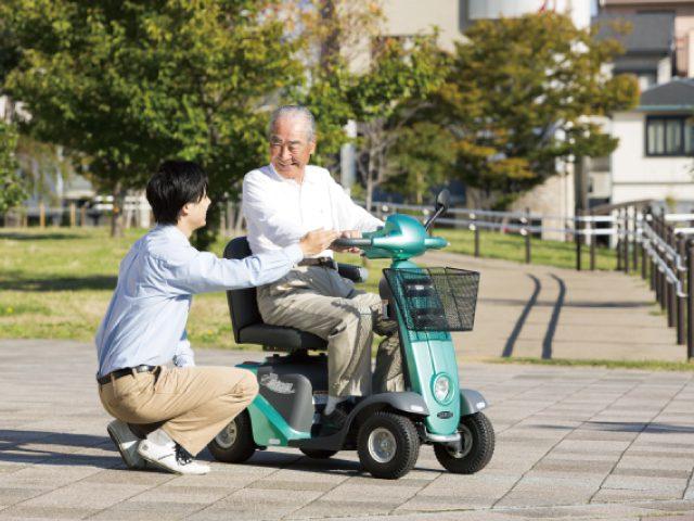 電動カートに乗るシニア男性と介助する男性
