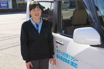 介護タクシーの側に立つ初任者研修(ヘルパー2級)の資格を持ったドライバー