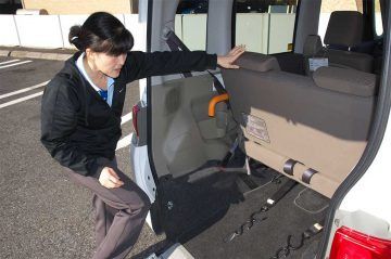 介護タクシーの内部を説明する女性ドライバー