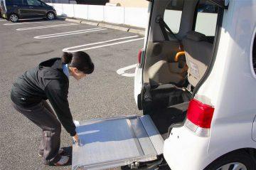 介護タクシー後部のスロープを出す女性